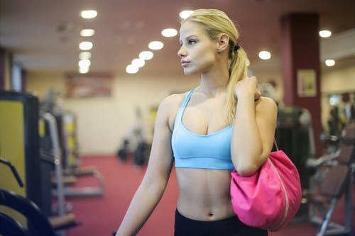 Woman in Blue Sports Bra Holding a Pink Bag