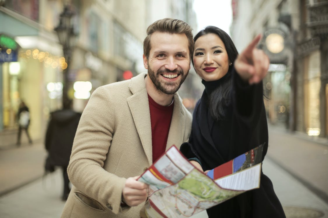 Man in Brown Suit Holding a Map Smiling Beside Woman in Black Coat
