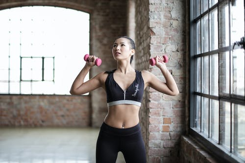Woman in Black Sports Bra and Black Leggings Holding Pink Dumbbells