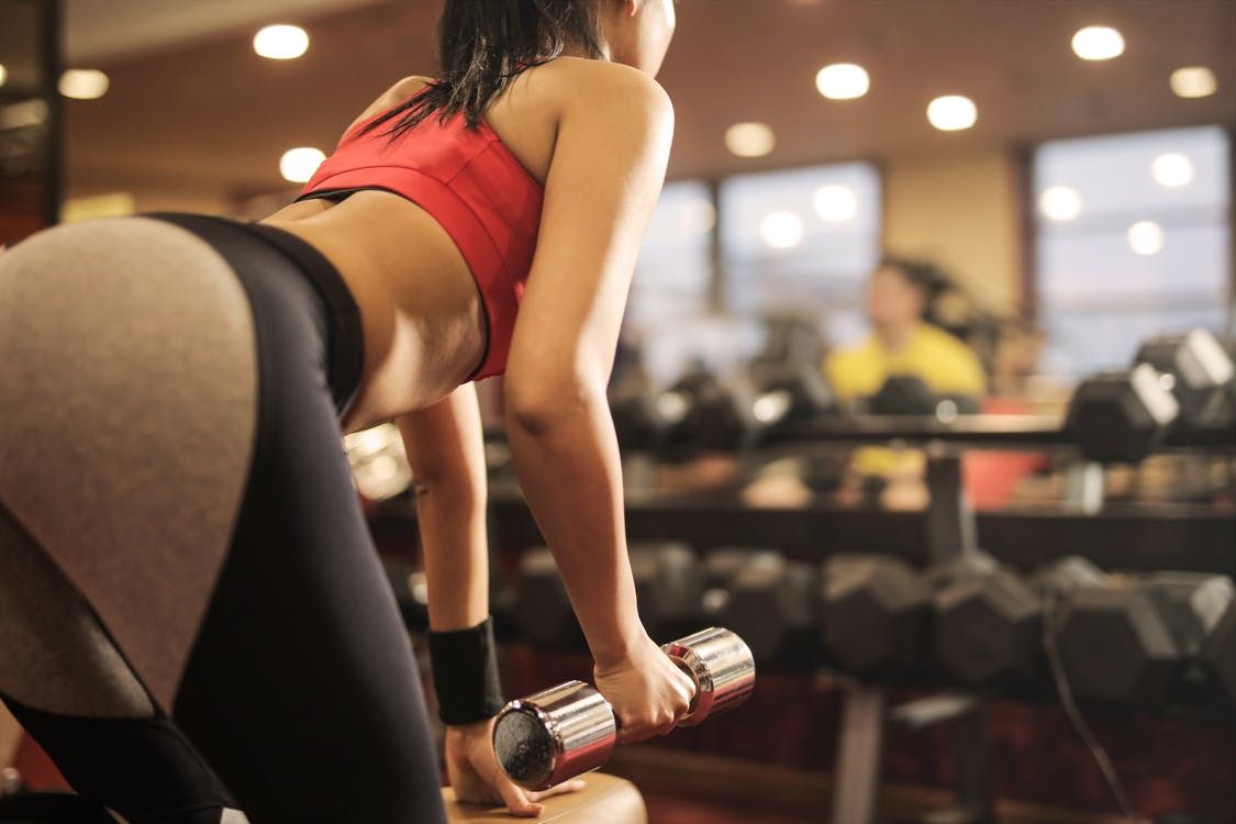 Woman in Red Sports Bra and Black Leggings Holding Black and Red Dumbbell