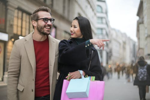 From below happy stylish Asian woman in warm clothes smiling at cheerful unshaven man in glasses and pointing finger away while walking along street together in city after shopping