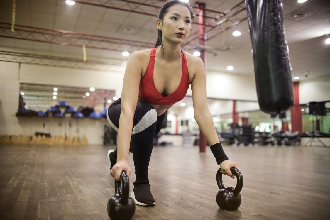 Strong determined ethnic woman stretching body using kettlebells.
