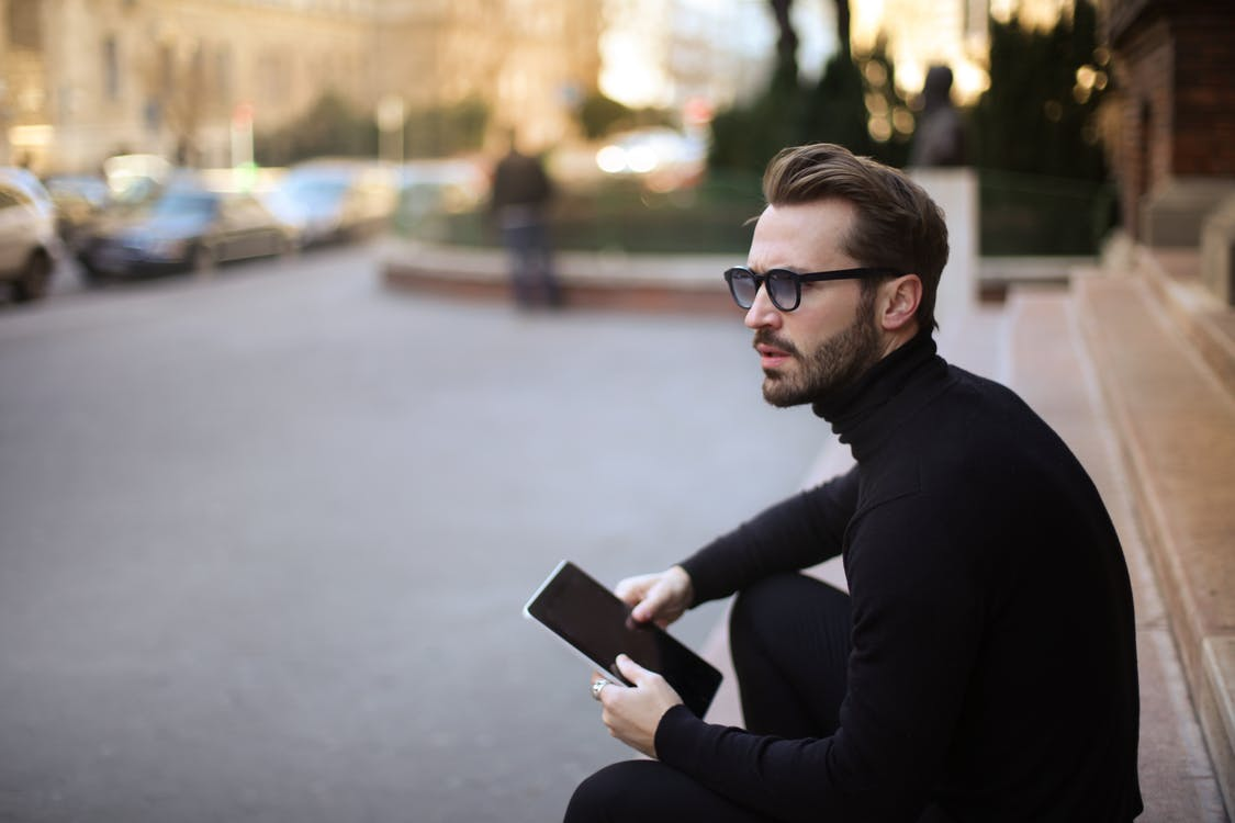 Side view of trendy serious bearded male in glasses and black casual clothes with notebook looking away and thinking while sitting on exterior stairs at entrance of modern building in downtown