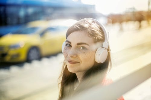 Happy young woman in headphones listening to music on street