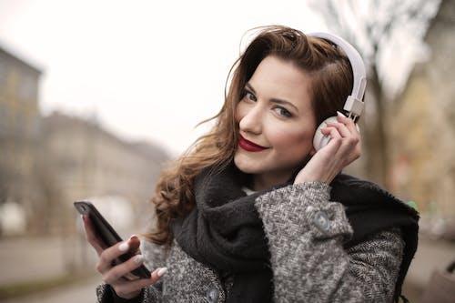 Uma Foto De Uma Mulher Ouvindo Música Em Fones De Ouvido Brancos