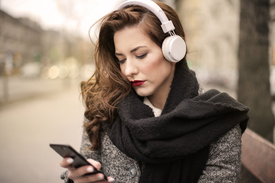 Woman in Black Scarf Holding Black Smartphone