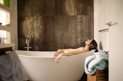 Woman Lying on Bathtub