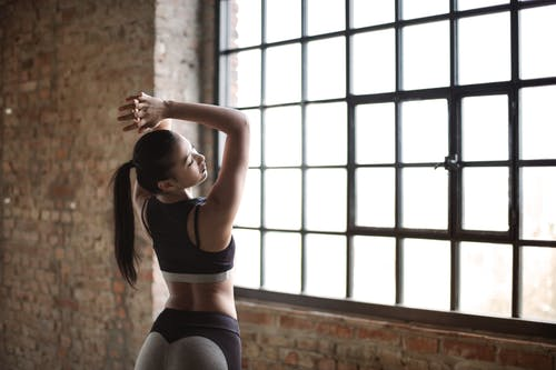 Woman in Black Sports Bra While Standing Near Window