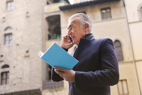 Man in Black Suit While Holding Blue Book