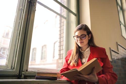 Mulher Vestindo Um Casaco Vermelho Enquanto Lê Um Livro