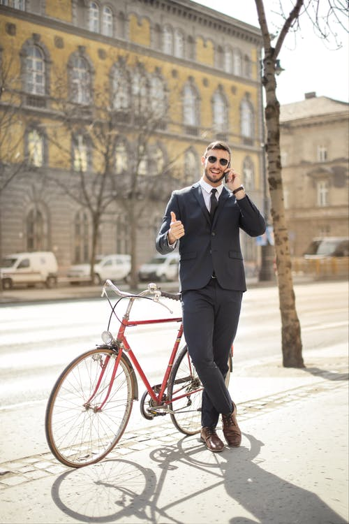 Man in Black Suit Standing Beside Red Bicycle