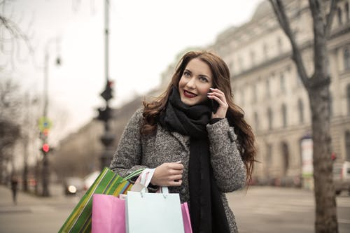 Happy adult woman in warm coat and scarf with shopping bags smiling away while standing on street and talking on phone against blurred urban environment in cool overcast weather