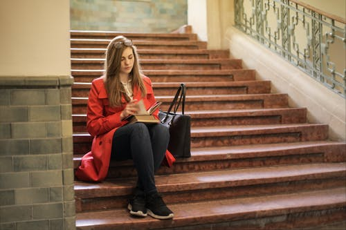 Woman in Red Jacket Sitting on Brown Staircase