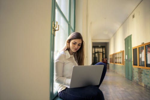 Woman in White Long Sleeve Shirt Using Macbook