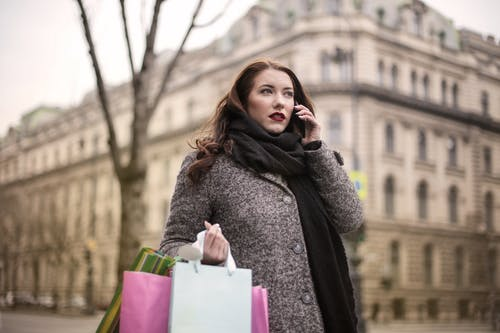 Woman Holding Shopping Bags While Using Her Smartphone