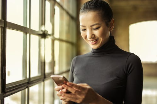 Woman in Black Turtleneck Holding Smartphone