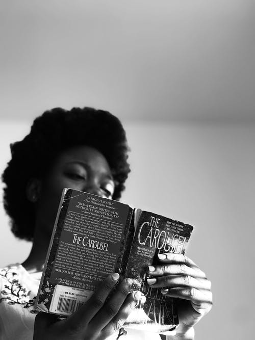 Grayscale Photo of Woman Holding Book