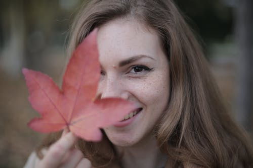 Close-Up Photo of Woman Holding Red Maple Leaf