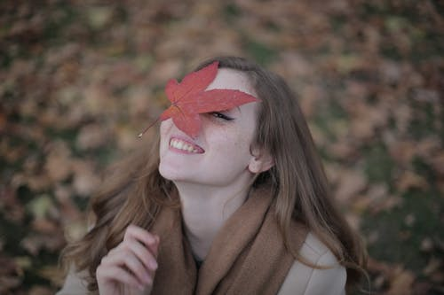 Woman in Brown Coat With Red Maple Leaf on Her Face