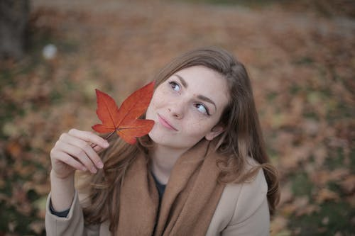 Woman in Brown Coat Holding Red Maple Leaf