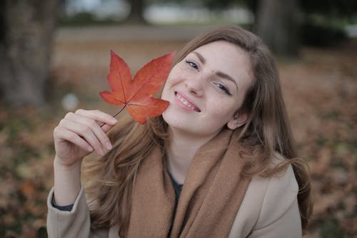 Happy millennial woman with red leaf enjoying autumn in park