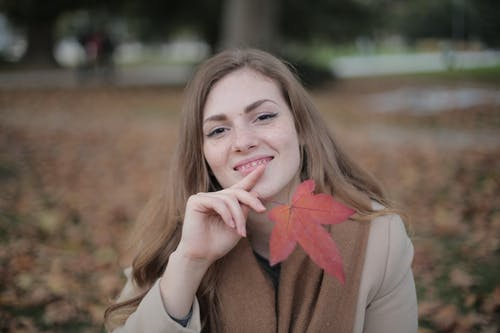 Attractive young lady in warm clothes and scarf with red maple leaf touching chin and smiling at camera against blurred environment in autumn park
