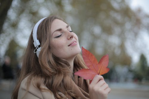 Young satisfied woman in headphones with fresh red leaf listening to music with pleasure while lounging in autumn park