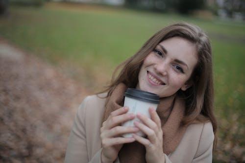 米色的长袖衬衫,拿着灰色杯的女人
