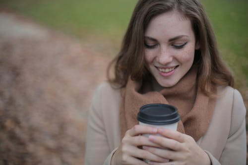 Smiling Woman Holding Black and White Disposable Cup