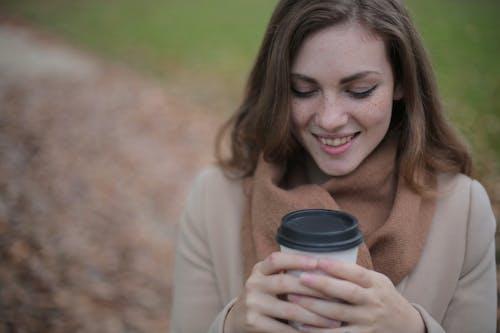 黒と白の使い捨てカップを保持している笑顔の女性