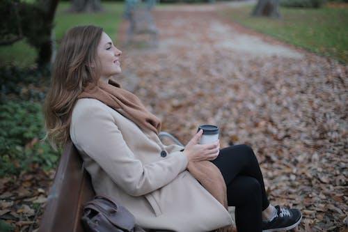 坐在長凳上的米色外套的女人