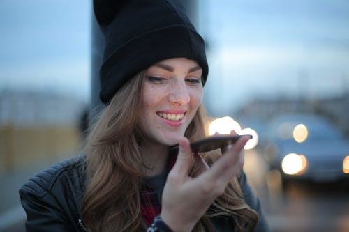 Woman in Black Knit Cap Holding Smartphone