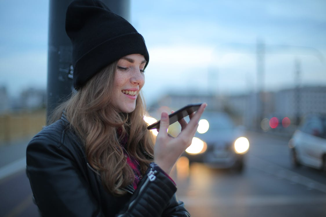 Woman in Black Knit Cap and Black Jacket Holding Smartphone