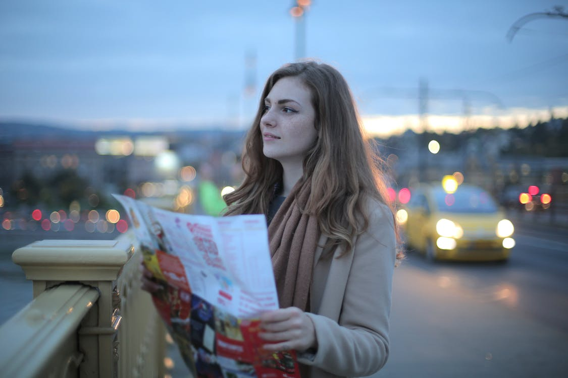 Female traveler in warm clothes standing on street with map and looking away at dusk