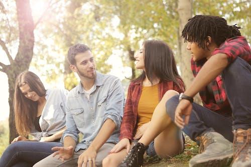 Happy multiethnic friends sitting in park