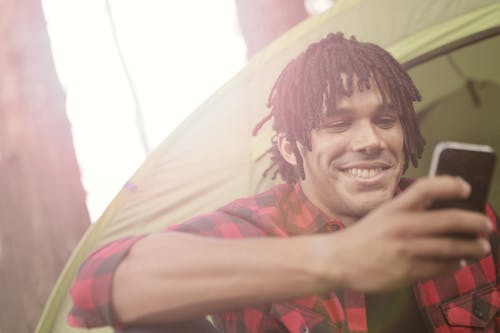 Young casually dressed man smiling while sitting near tent and surfing smartphone in back lit