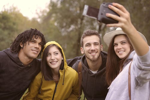 Happy diverse friends taking selfie in park