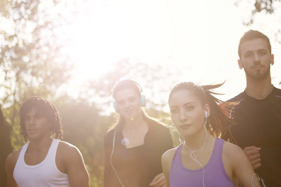Group of young multiracial women with earphones and men in sportswear running together on sunny day in park