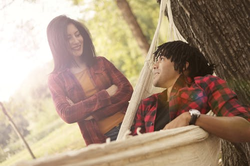 Cheerful young woman with crossed arms standing next to ethnic friend while man lying on hammock in park