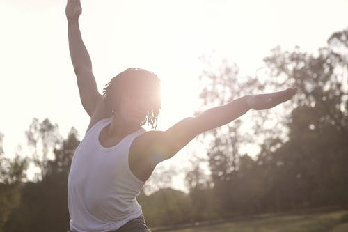 Sportsman in undershirt raising arms while doing exercises in sunny day in park