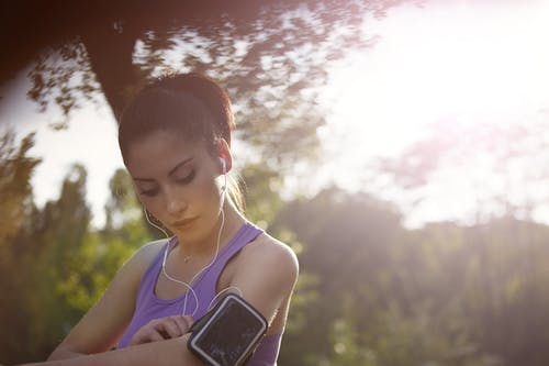 Young sportswoman listening to music in park