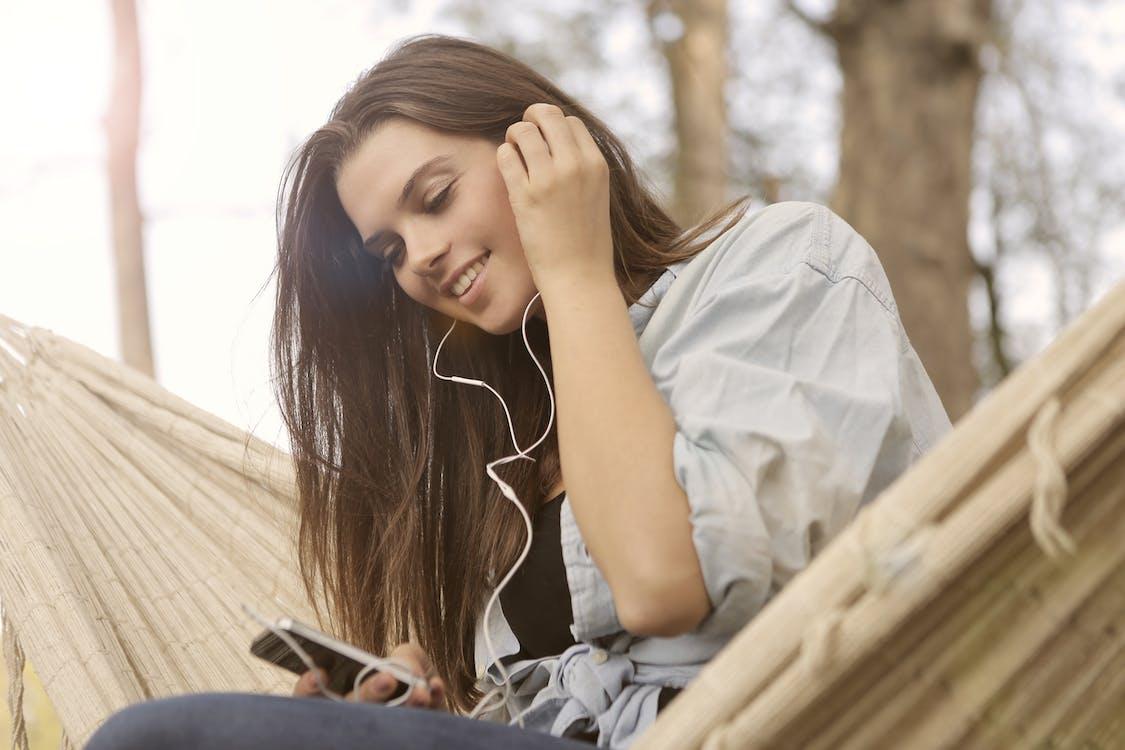 Mujer En Camisa Blanca Con Botones Mientras Escucha Música