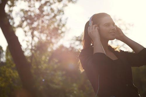 音楽を聴きながら黒の長袖シャツを着た女性