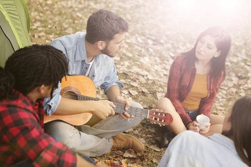 Man Playing Acoustic Guitar Sitting on Grass Field