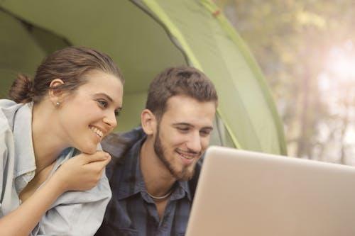 Woman in Denim Long Sleeves Beside Man Using Laptop