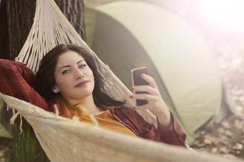 Woman Lying on Hammock While Using Cellphone