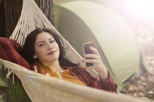 Donna Sdraiata Sull'amaca Durante L'utilizzo Del Cellulare