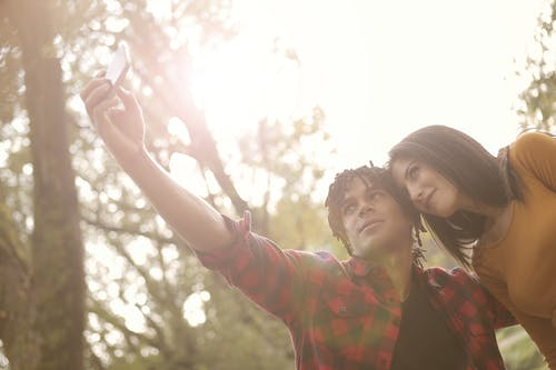 Man and Woman Taking Selfie Using Smartphone