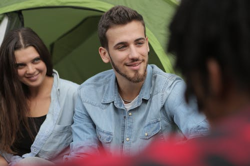 Happy couple sitting in front of tent