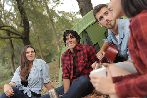 Happy multiethnic friends resting in park with guitar